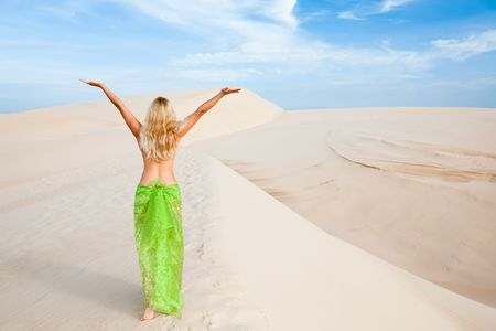Nude woman with hands up in the middle of desert. Rear view photo