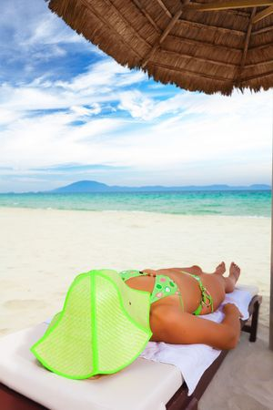 sunburned: Young woman sunbathing on the chair near the ocean