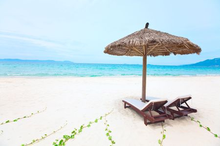 daybed: Sandy tropical beach with deck chairs in sunny day