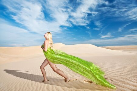 Beautiful nude woman with scarf in desert photo