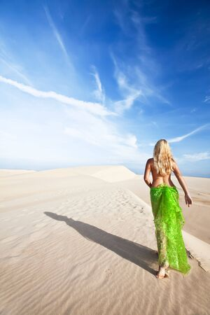 Woman walking in the middle of desert photo