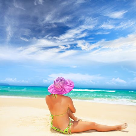 Woman in pink hat is sitting on the beach photo