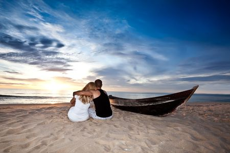 Romantic couple and boat on the beach at sunrise time photo