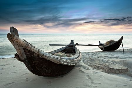 old boat: Two fisherman boats at sunrise time on the beach