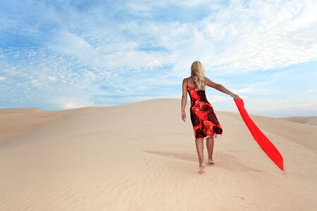 Young woman with red scafr walking alone in desert photo