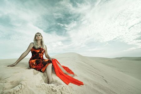 Young woman sitting alone in desert. Retro style photo