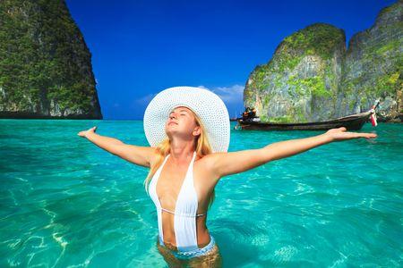 Happy woman with opened hands at Maya bay. Thailand photo