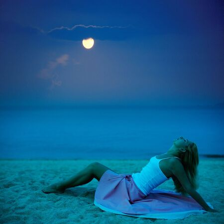Young beautiful woman posing on the beach at night time photo