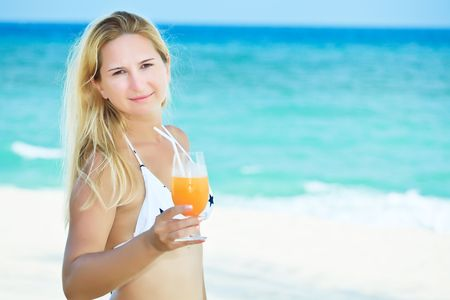 Wiman with juice on the tropical beach photo