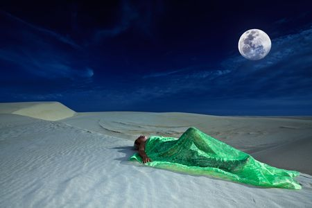 gobi desert: Beautiful woman sleeping in desert under moonlight Stock Photo