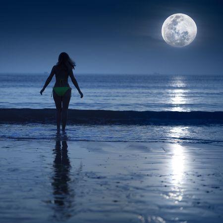 Mujer va a nadar bajo la luz de la Luna