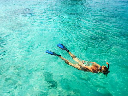 Young woman is snorkeling in tropical lagoon