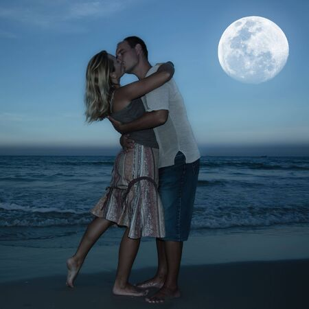 love kissing: Young couple kissing at the beach under moonlight