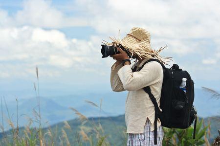 Turistica con fotocamera tenendo foto delle montagne