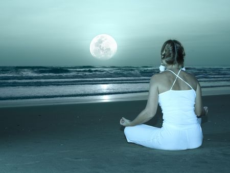 Woman is meditating at twilight time under moon photo