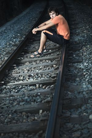 return trip: Young handsome men is sitting on train track