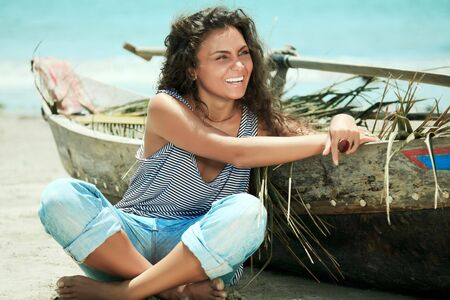 Young beautiful fisherwoman with boat on the beach photo