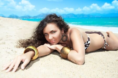 Young beautiful woman is sunbathing on the beach photo