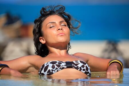 Young woman is relaxing in swimming pool photo