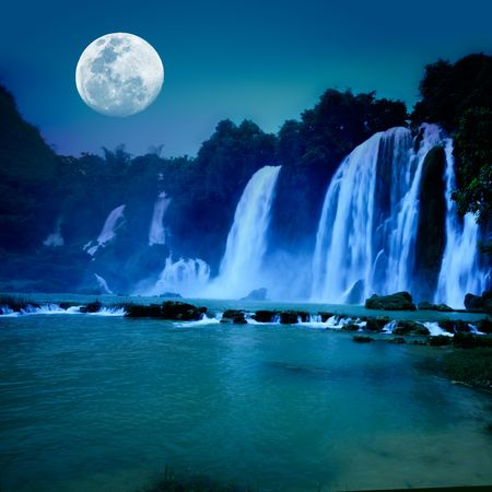 Beautiful waterfall under moonlight at night time photo