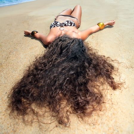curly hair model: Young beautiful woman is sunbathing on the sand