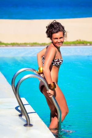Young beautiful smiling woman in swimming pool photo