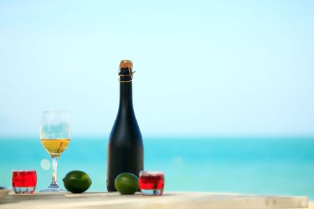 Bottle and glass of wine on the beach Imagens