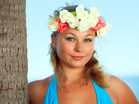Woman is posing near the trunk of palmtree photo