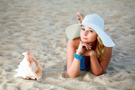 Young woman sunbathing on the tropical beach photo