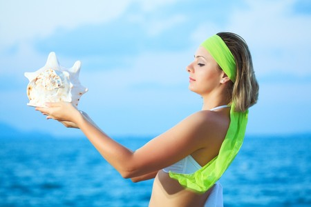 Young beautiful woman with seashell in her hands photo