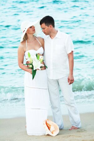 Romantic couple near the ocean with flowers photo