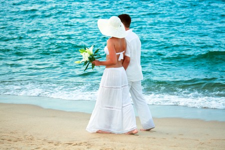 Romantic young couple walking along the sea photo