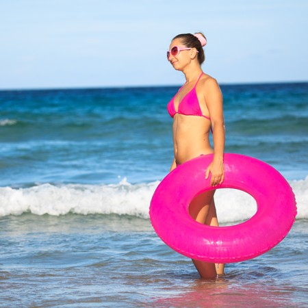 Woman with inner tube on the tropical beach photo