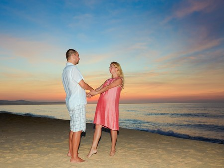 Romantic couple on the beach at sunrise time. photo