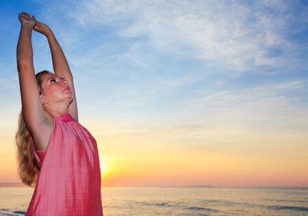 Young woman enjoy sunrise on the beach photo