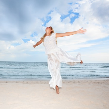 Young woman in white dancing on the beach photo