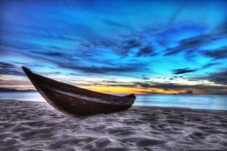 Old fisherman boat at sunrise time on the beach photo