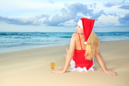santa lingerie: Miss Santa sitting near the ocean with glass of wine