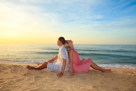 Couple sitting on the beach at sunrise time. photo
