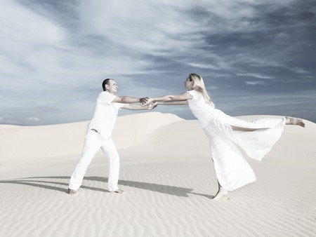 a marriage meeting: Young couple dancing on desert dune at wedding date