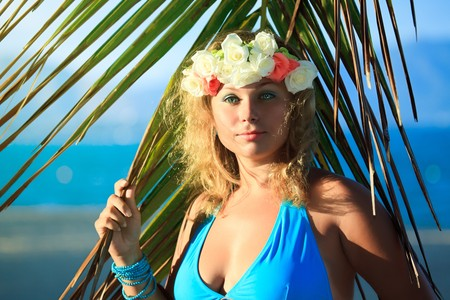 Woman in flower diadem on the beach photo