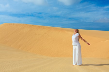 Beautiful woman with opened nahds in desert photo
