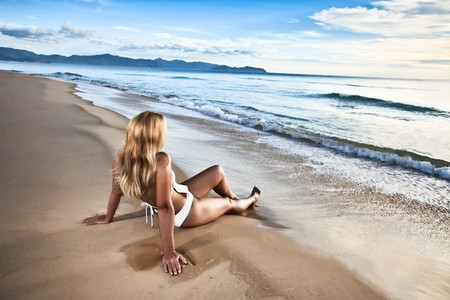 Rear view of woman on the beach at sunrise time Stock Photo - 7598383