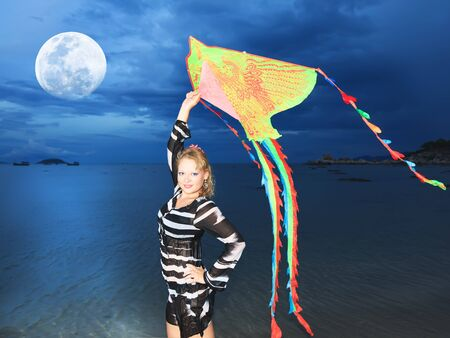 Beautiful woman with kite on the beach under moon photo