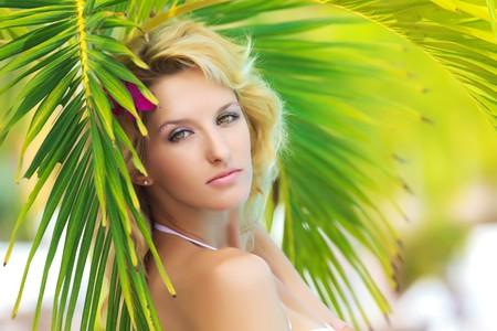 Portrait of a beautiful woman under palm tree photo