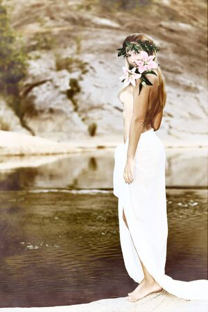 Beautiful woman as a forest nymph on the river photo