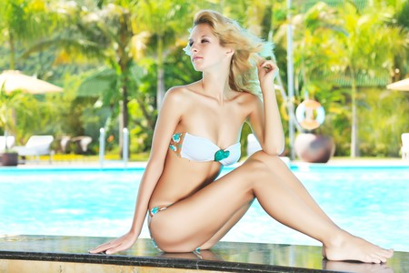Beautiful woman sitting on the edge of swimming pool  photo