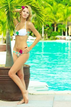 Beautiful woman near swimming pool under palm tree photo