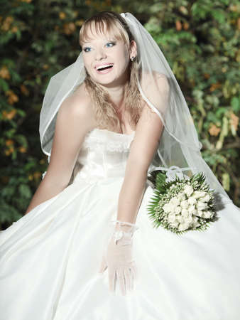 Beautiful young bride in wedding dress outdoor photo