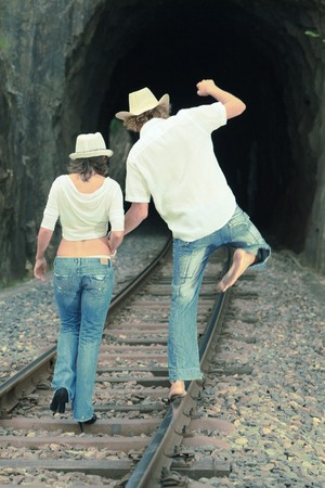 Young couple posing on a train tracks photo